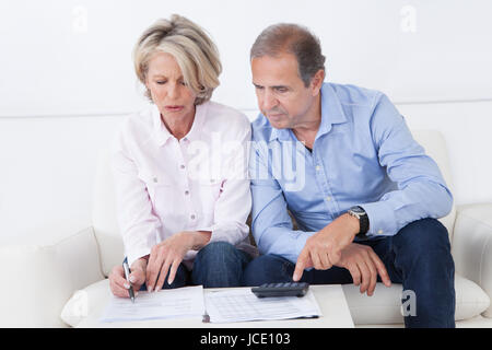Mature couple doing family finances at home - Stock Photo