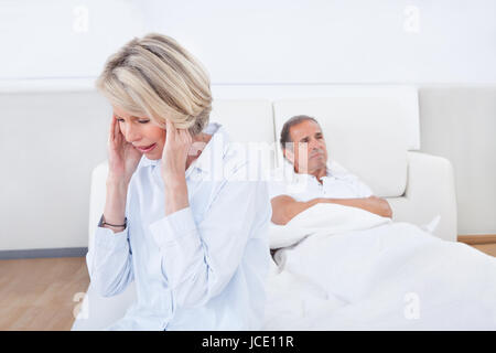 Sad Woman Sitting At The Edge Of Bed In Front Of Man - Stock Photo
