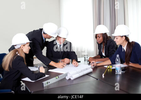 ... Successful group of mature architects discussing about the changes on  the blueprint - Stock Photo