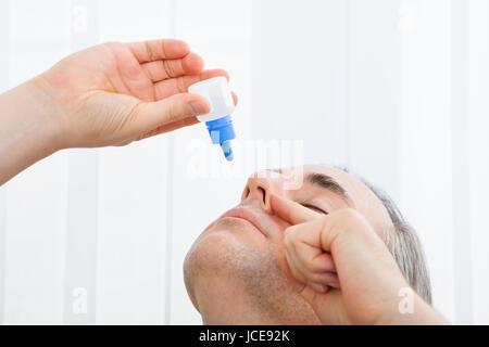 Close-up of a man using nasal spray; indoors - Stock Photo