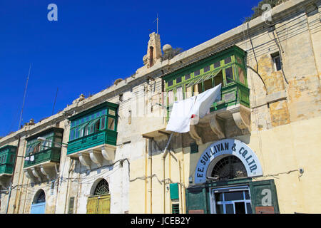 Old merchant house with balcony above warehouse area, Valletta, Malta - Stock Photo