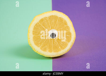 Minimal still life photography.An lemon cut in half and wearing doll's eyes like a cyclop. pop bi colored background - Stock Photo