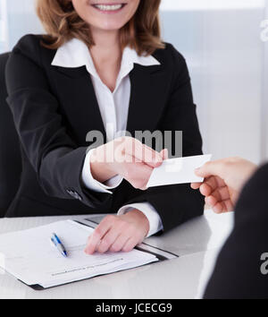 Two happy businesspeople exchanging visiting card in office - Stock Photo