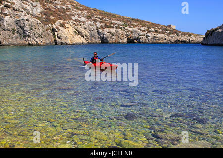 Kayaking shoreline clear blue sea water, Mgarr ix-Xini coastal inlet, island of Gozo, Malta - Stock Photo