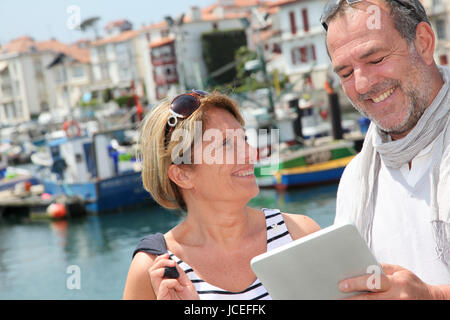 Senior couple using digital tablet to find city tour - Stock Photo
