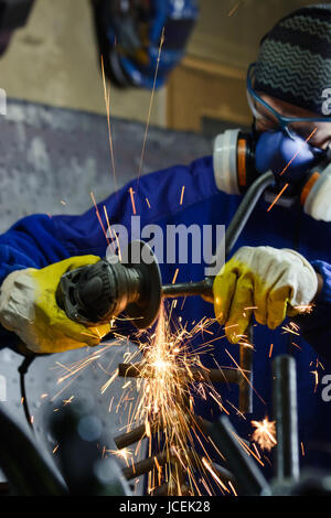 Metal grinding on steel pipe with flash of sparks close up - Stock Photo