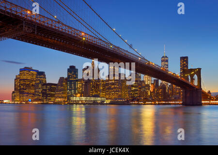 Brooklyn Bridge with the New York City skyline in the background, photographed at dusk. - Stock Photo