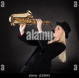 Beautiful young woman playing saxophone over black background - Stock Photo