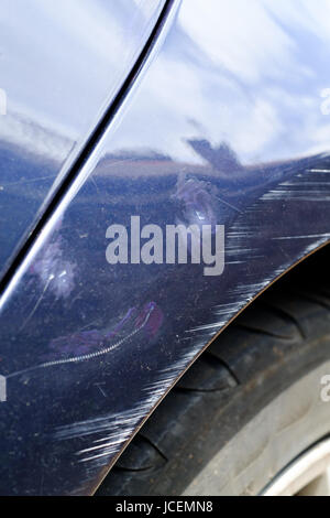 Scratches and minor dents on front wing of blue coloured road car. - Stock Photo