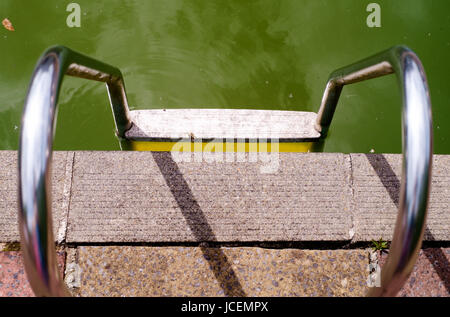 Handrails and combined steps by an outdoor swimming pool where the algae in the water has caused it to turn green. - Stock Photo