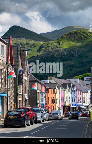 Colourful Llanberis High Street backed by Mount Snowdon, Snowdonia National Park, North Wales, UK - Stock Photo