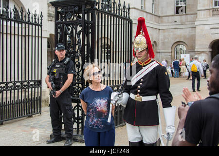 London, UK. 14th June, 2017. A tourist poses next to a footguard, sword drawn, from the Household cavalry, Blues - Stock Photo