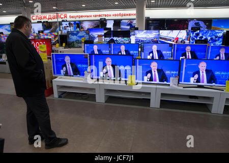 Moscow, Russia. 15th June, 2017. A customer watches TV as Russian President Vladimir Putin speaks during a televised - Stock Photo