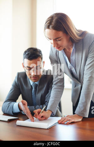 Businessman explaining to his secretary how to fill in the paper in office - Stock Photo