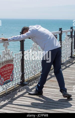 A single asian man stretching his arms out on the railings on the famous victorian landmark, Brighton Palace Pier. - Stock Photo