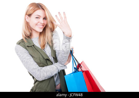 Cheerful pretty lady rising three fingers and holding shopping bags on white background with copyspace - Stock Photo