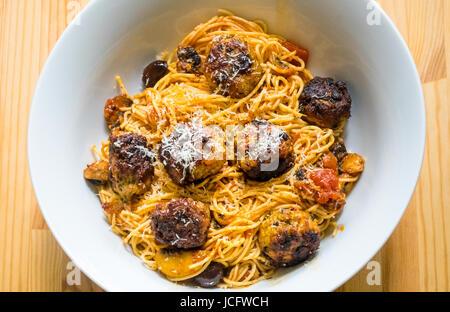 Spaghetti and Italian meatballs in a white bowl - Stock Photo