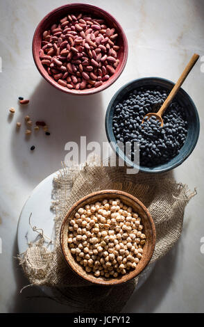 Garbanzo beans/chickpeas,kidney beans/rajma,black beans in individual ceramic bowls on a marble table on top view - Stock Photo