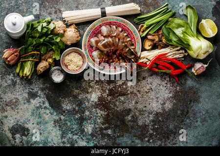 Ingredients for cooking Asian food with Tiger shrimps, udon noodles, mushrooms, greens, vegetables, spices on metal - Stock Photo
