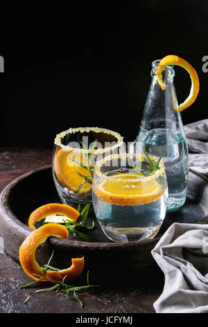 Tonic water cocktail with rosemary and orange. Two glasses and bottle with zest sugar and bubbles in terracotta - Stock Photo