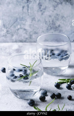 Tonic water cocktail with rosemary and blueberries. Two cold glasses over gray blue texture background. Refreshing - Stock Photo