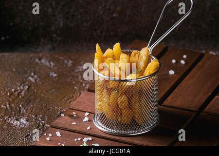 Traditional french fries potatoes served in frying basket with salt, thyme on wooden board over brown texture background. - Stock Photo