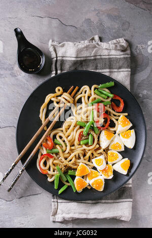 Cooking stir fry udon noodles, green beans, sliced paprika, boiled eggs, soy sauce with sesame seeds in black plate - Stock Photo