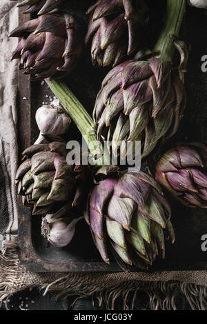 Uncooked whole organic wet purple artichokes with garlic in old rusty oven tray on textile sackcloth over dark wooden - Stock Photo