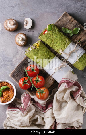 Green spinach matcha tortillas wrapped in paper with ingredients above. Sweet corn, avocado, green paprika, sprouts, - Stock Photo