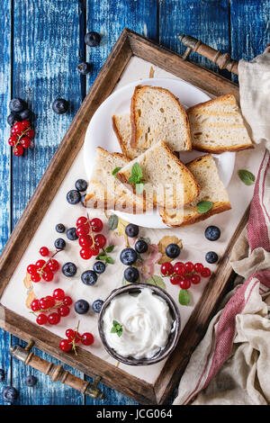 Variety of ingredients for making dessert sandwiches with bread, berries, cream cheese. Red currant, blueberries, - Stock Photo