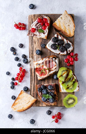 Variety of dessert sandwiches with berries and cream cheese and chocolate swirl. Red currant, blueberries, sliced - Stock Photo