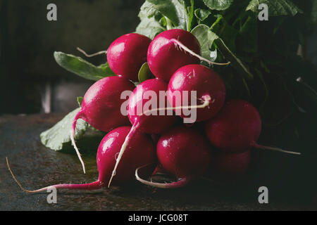 Fresh organic ripe young radish bundle with leaves over dark texture background. Close up. Selective focus, toned - Stock Photo