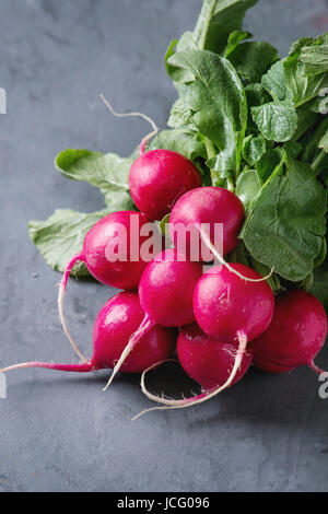 Fresh organic ripe young radish bundle with leaves over gray blue texture background. Close up - Stock Photo