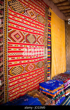 Traditional Moroccan shop with oriental stacked fabrics in Ouarzazate, Morocco - Stock Photo