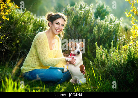 Girl walking with a hunting dog - the Jack Russell Terrier . Close-up. Spring. Copy space. - Stock Photo