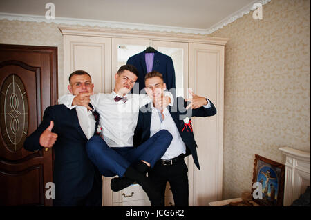 Handsome groom and groomsman in the room hugging next to the mirror. - Stock Photo