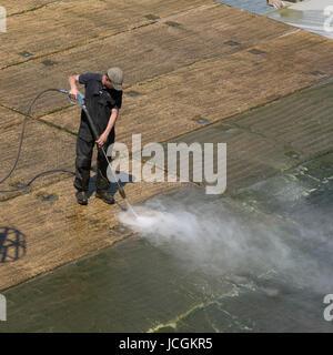 Man using a waterjet to clean green algae from a concrete marina slipway. Dorset England UK June 2017 - Stock Photo