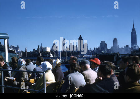 Antique October 1958 photograph, tour group and the New York City skyline on a Circle Line tour boat on the Hudson - Stock Photo