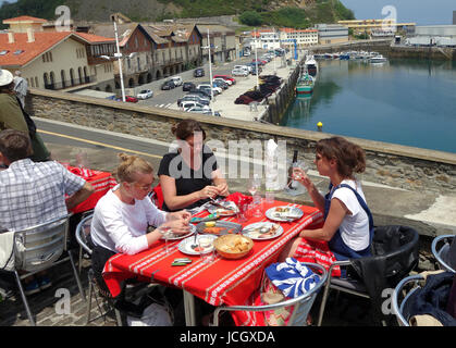 People eating dining outside at Getaria in the province of Gipuzkoa,  Basque Country in Northern Spain - Stock Photo