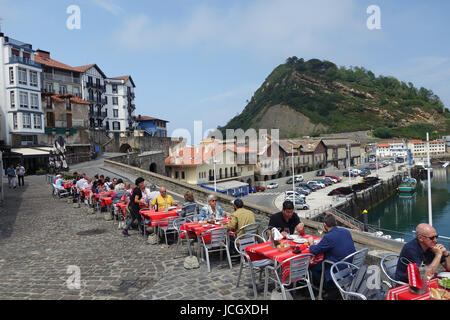 People eating dining outside at Getaria in the province of Gipuzkoa,  Basque Country in Northern Spain. - Stock Photo