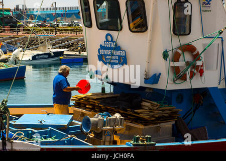 A deck hand works on a local fishing trawler berthed in the crowded harbor in Los Cristianos in Spanish Island of - Stock Photo