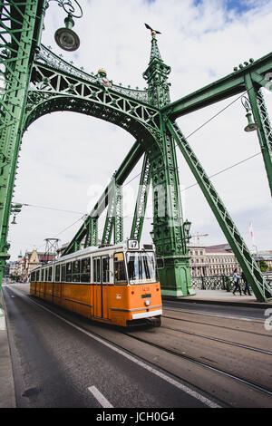 Moving yellow tram on the Liberty Bridge or Freedom Bridge, Budapest, Hungary - April 2017. - Stock Photo