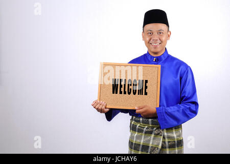 Young man smiling with chalkboard for Eid Fitr or Eid Adha celebrations. - Stock Photo