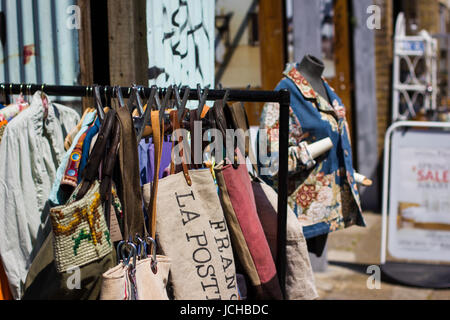 Vintage and secondhand clothes and objects jostle for space athe Columbia Road Flower Market, London - Stock Photo