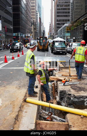 NEW YORK CITY - OCTOBER 15, 2014: construction workers doing repair work on supply lines in the underground of Madison - Stock Photo