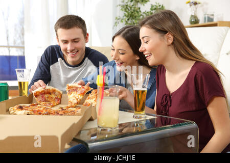Three friends talking and eating pizza sitting on the floor of the living room at home - Stock Photo