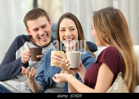 Three happy friends talking and laughing loud holding drinks sitting on a sofa in the living room at home - Stock Photo