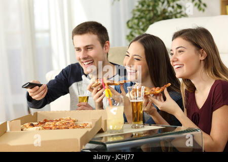 Three friends watching tv and eating pizza sitting on the floor in the living room in a house interior - Stock Photo
