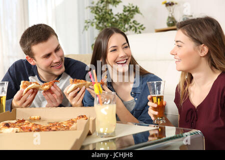 Three friends talking and eating pizza sitting on the floor in the living room at home - Stock Photo