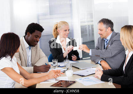 Businesspeople In A Meeting Exchanging Visiting Card - Stock Photo